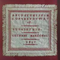 額装されたアルファベット刺繍サンプラー