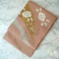 【なごや帯】珊瑚色地に椿柄染め名古屋帯