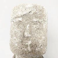 Carved stone face sculpture