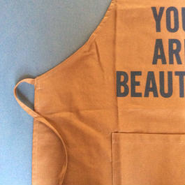 "DRESSSEN DR(BRN)2  APRON ""YOU ARE BEAUTIFUL ""BROWN COLOR"