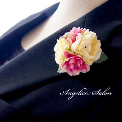 プティブーケのコサージュ。ピンクとイエローのバラのまるいラウンドコサージュ 入学式・結婚式すすめ