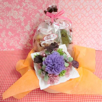 陶器のフレームに四つ葉のクローバーをあしらった紫色カーネーションのプリザーブドフラワーアレンジと野菜や果物を使った焼き菓子8袋のギフトセット