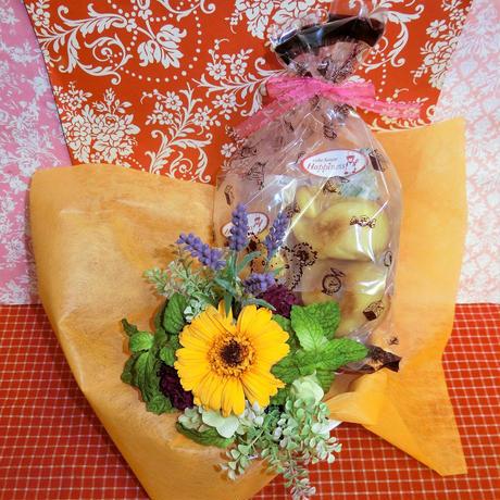 パープルのブリキの器にアレンジしたガーベラのプリザーブドフラワーと野菜や果物を使った焼き菓子6袋のギフトセット