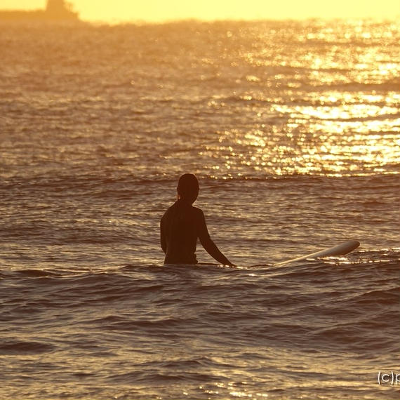 朝焼けの中、波間に浮かぶ女性サーファー(1)[商用利用OK]