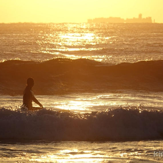 朝焼けの中、波間に浮かぶ女性サーファー(2)[商用利用OK]