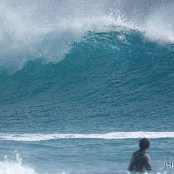 荒れて波が高い海に海を見つめるサーファーの姿。[商用利用OK]