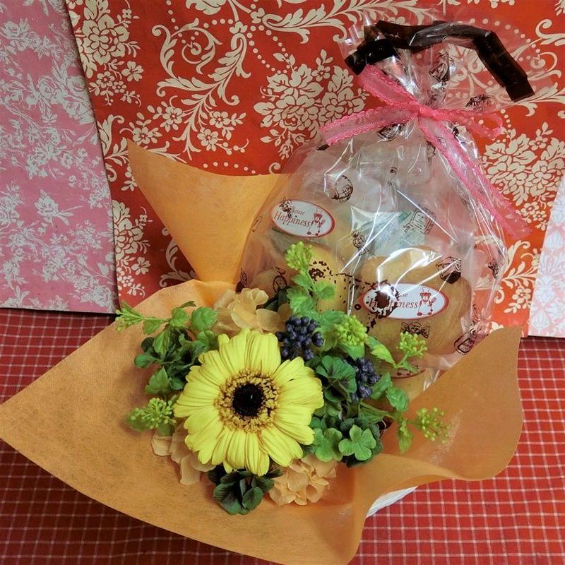 ガーベラのプリザーブドフラワーに四つ葉のクローバーをあしらったアレンジと野菜や果物を使った焼き菓子6袋のギフトセット