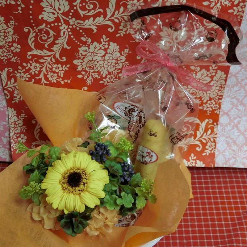 ガーベラのプリザーブドフラワーに四つ葉のクローバーをあしらったアレンジと野菜や果物を使った焼き菓子2袋のギフトセット(^^♪