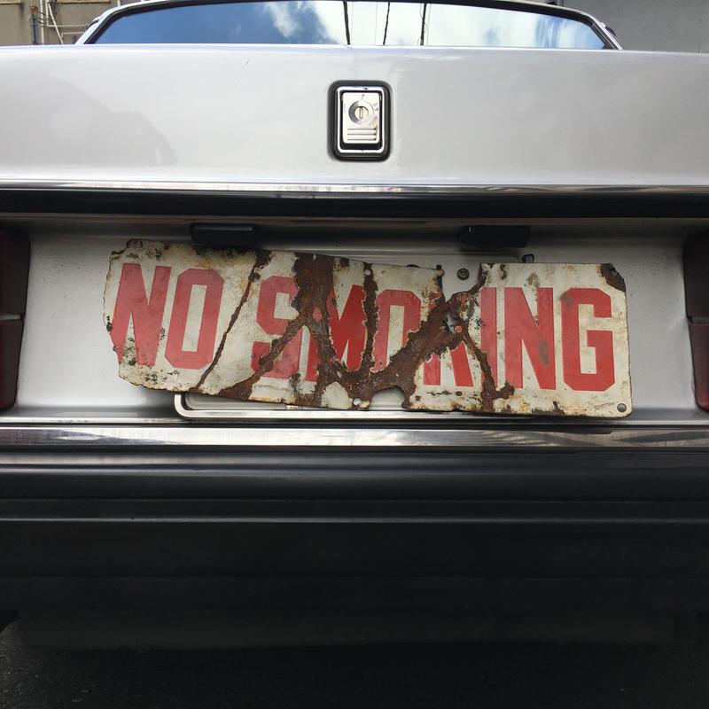 Beat up no smoking  sign