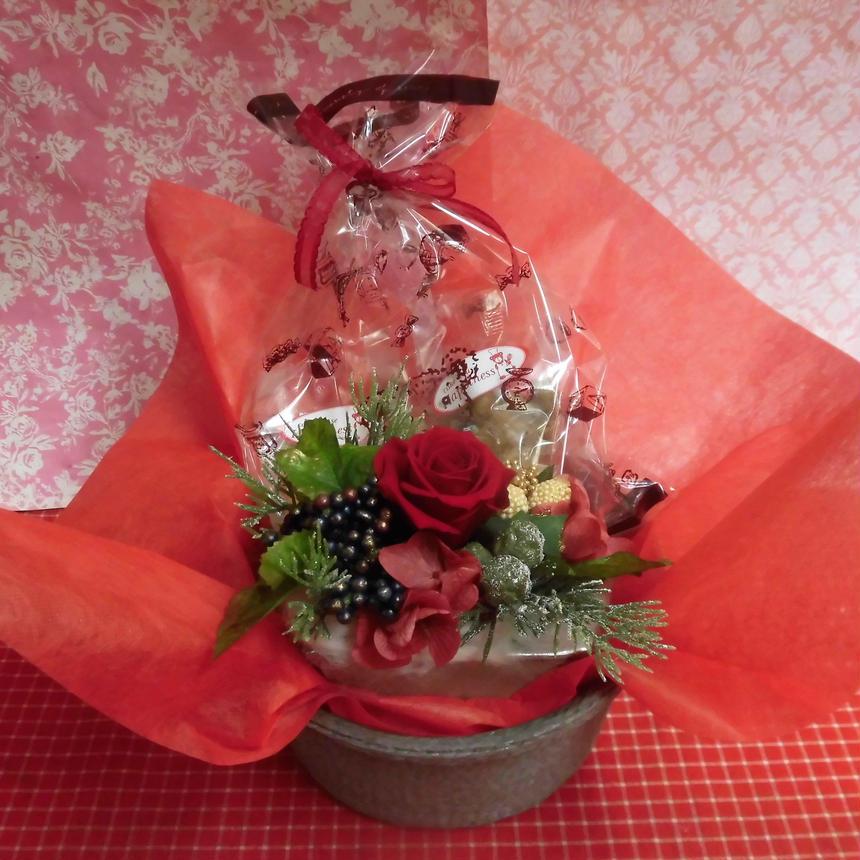 銀縁に輝いた陶器にクリスマスアレンジした薔薇のプリザーブドフラワーアレンジと冬の焼き菓子2袋のギフトセット